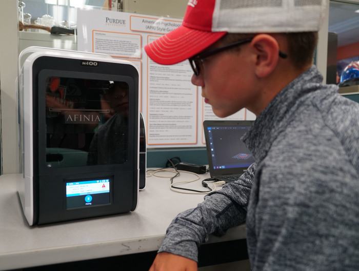 student looking at 3D printer