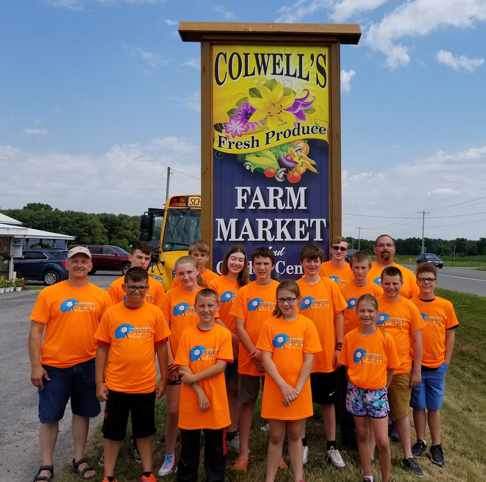 Camp students in front of farm market sign