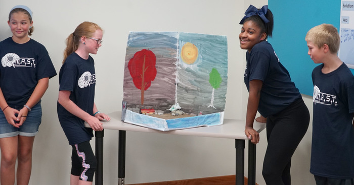students present their beach poster they created