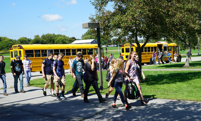 students walking towards school with buses in background