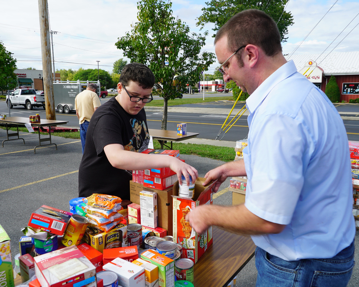 student helps organize donated food items