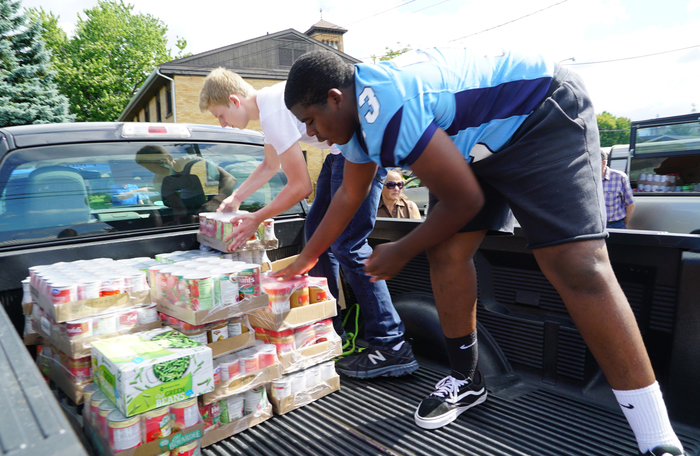 students load donated food items on truck