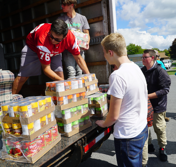 students load donated food items in back of van