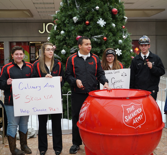 students in front of red kettle at mall