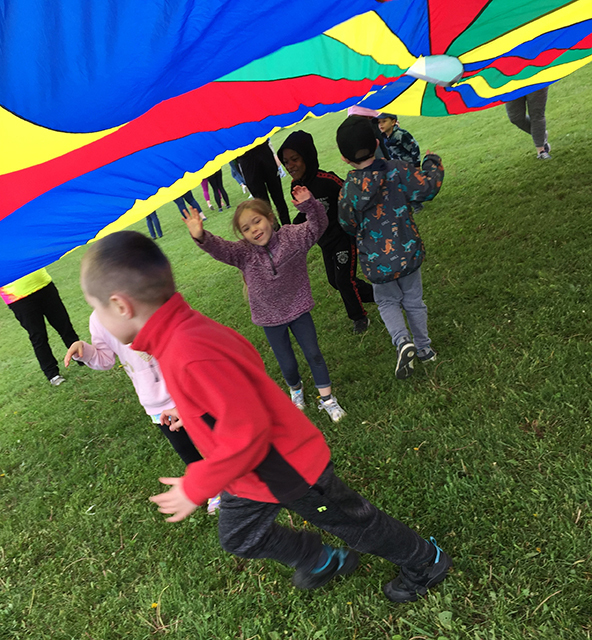 students playing under parachute