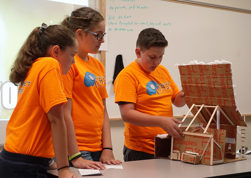 students showing their sugar shack prototype
