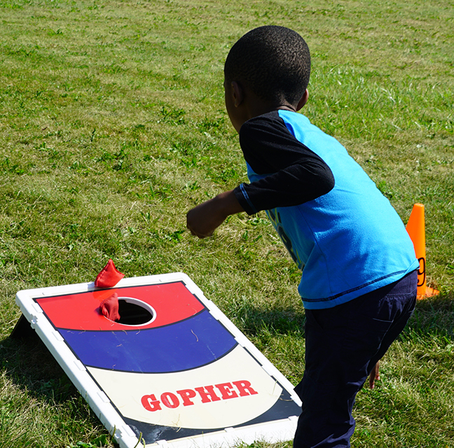 kid playing bean bag toss