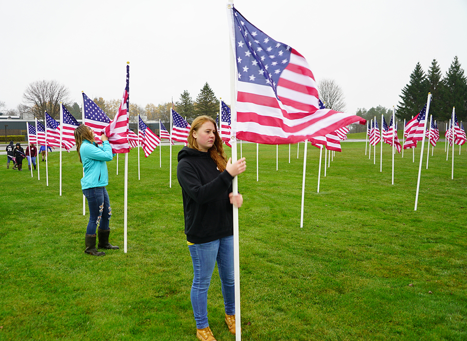 students placing flags in display