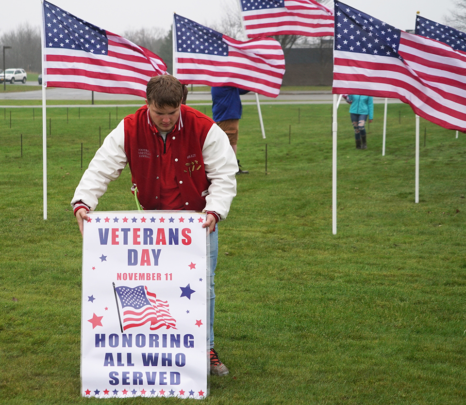 student placing display sign for veteran's day