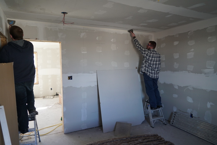 students placing drywall on duplex wall