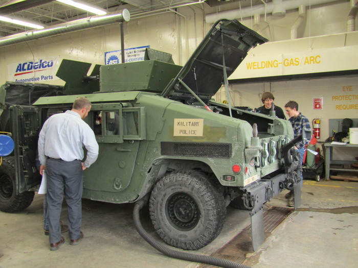 Students look at humvee