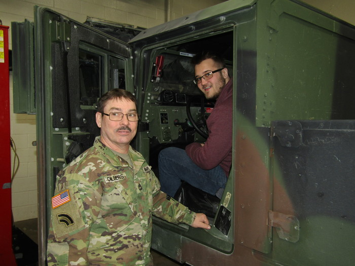 Army representative and student in humvee