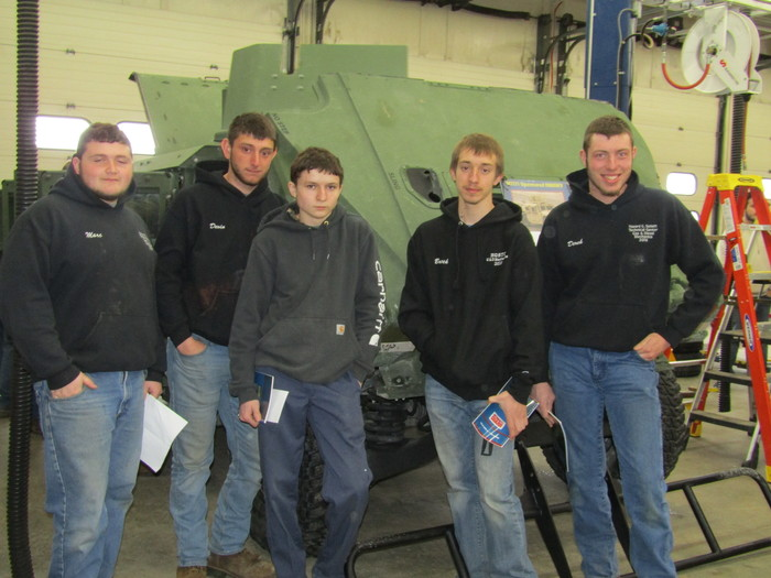 students pose near humvee