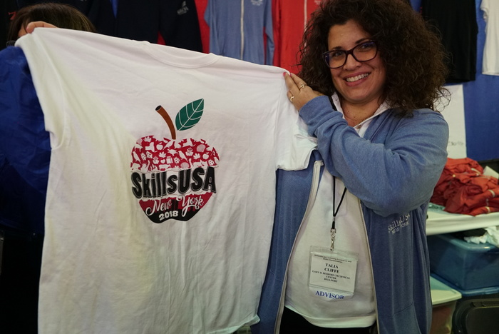 Woman holding up t-shirt with SkillsUSA apple logo