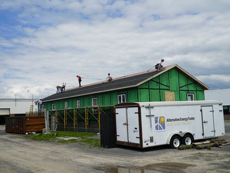 Students installing roof on duplex