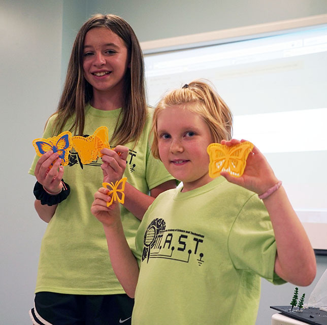 students hold 3D models of butterflies
